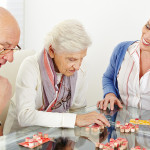 Senior couple playing Bingo with eldercare assistant in nursing